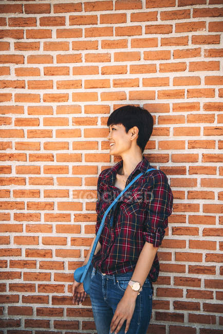 Короткие волосы азиатская женщина позирует перед камерой на кирпичной стене — стоковое фото