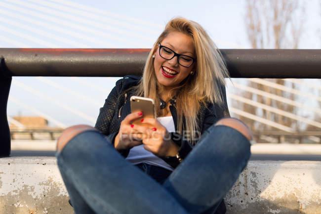 Портрет красивой молодой женщины с помощью мобильного телефона на улице . — стоковое фото
