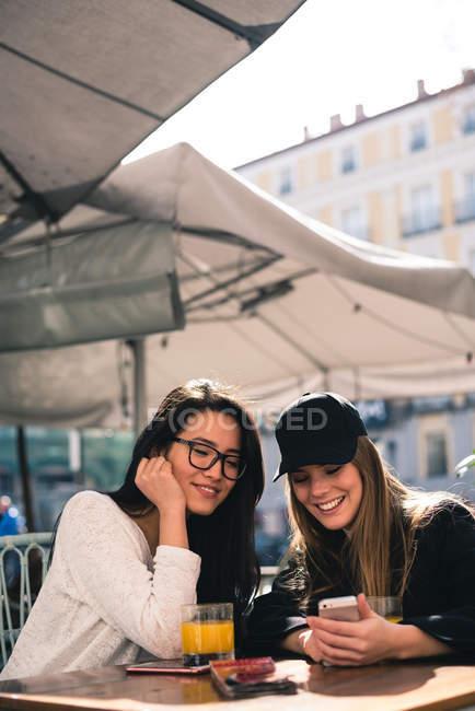 Две красивые подруги используют смартфон в кафе — стоковое фото