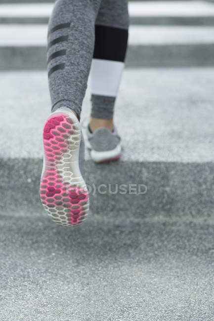 Cropped image of pair of legs running over concrete steps outdoors. — Stock Photo