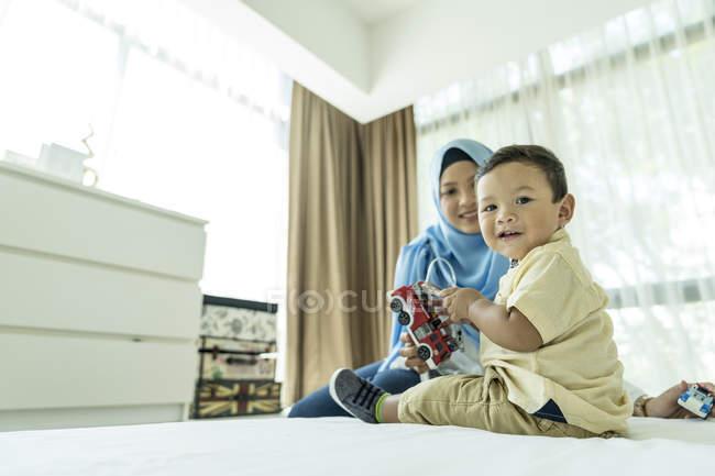 Jovem mãe muçulmana asiática e criança se divertindo em casa — Fotografia de Stock