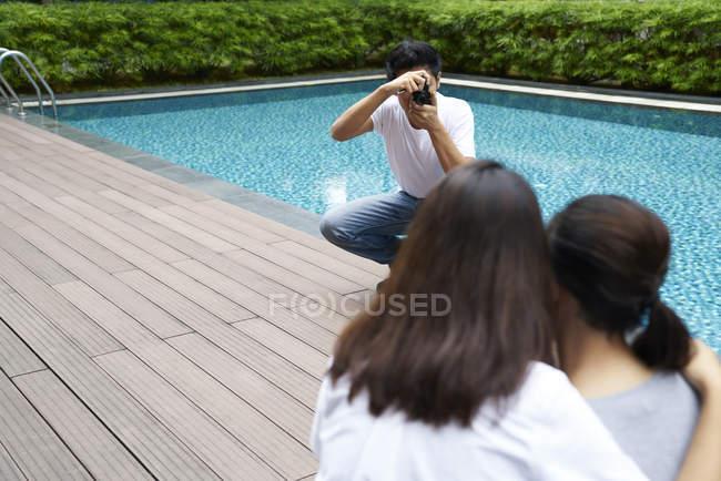 Fotografo che fotografa due modelli in un resort — Foto stock