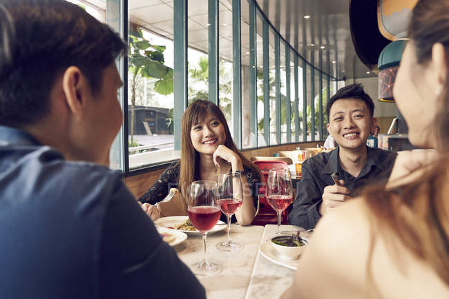 Happy young asian friends together in cafe — Stock Photo