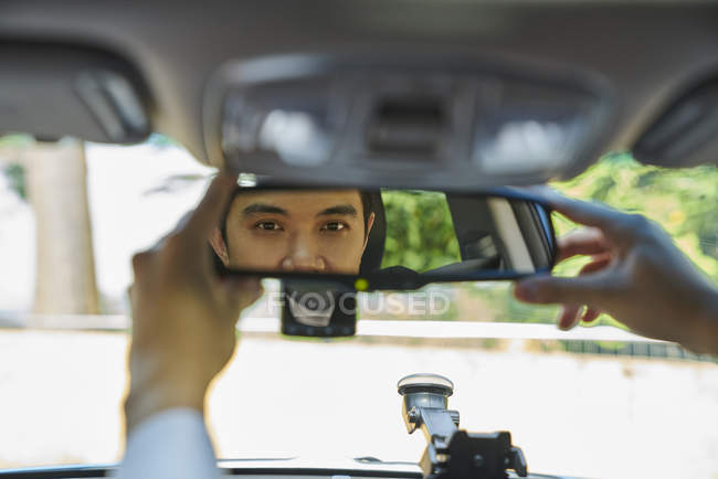 Young driver adjusting his rear view mirror — Stock Photo