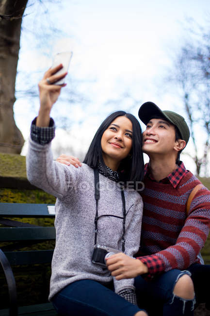 Young asian couple of tourists taking selfie in central park, New York, USA — Stock Photo