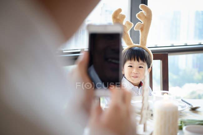Feliz asiático padre tomando foto de hijo en Navidad en casa - foto de stock