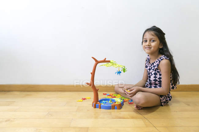 Young little cute asian girl playing with toys on floor — Stock Photo