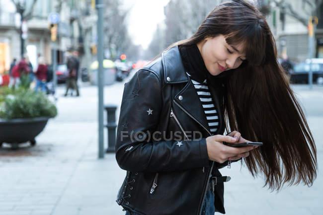 Молодий привабливою азіатські жінки в місті за допомогою смартфона — стокове фото