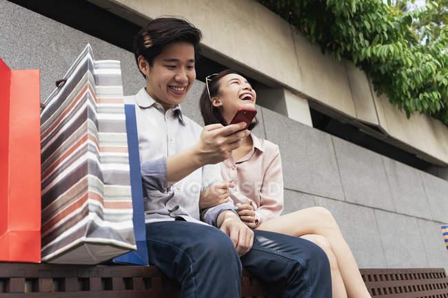 Joven asiático pareja usando smartphone juntos - foto de stock