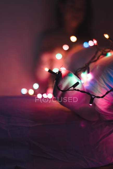 Cropped image of woman relaxing at home with Christmas garland — Stock Photo