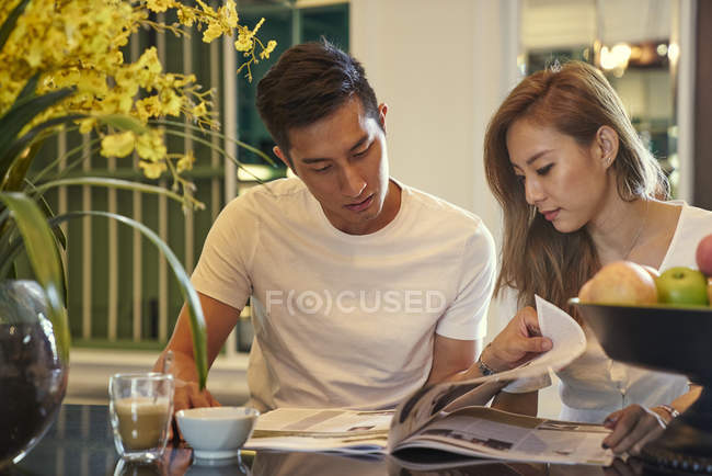 Happy young asian couple sitting together in cafe and reading magazine — Stock Photo