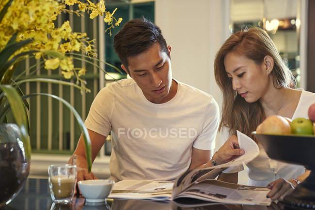 Glückliches junges asiatisches Paar sitzt zusammen im Café und liest Zeitschrift — Stockfoto