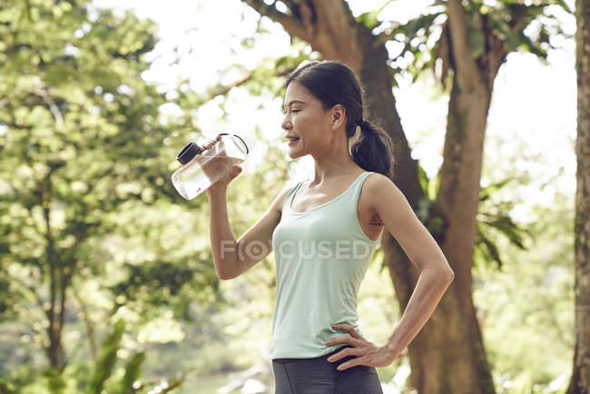 Женщина увлажняется после тренировки в Ботаническом саду, Сингапур — стоковое фото