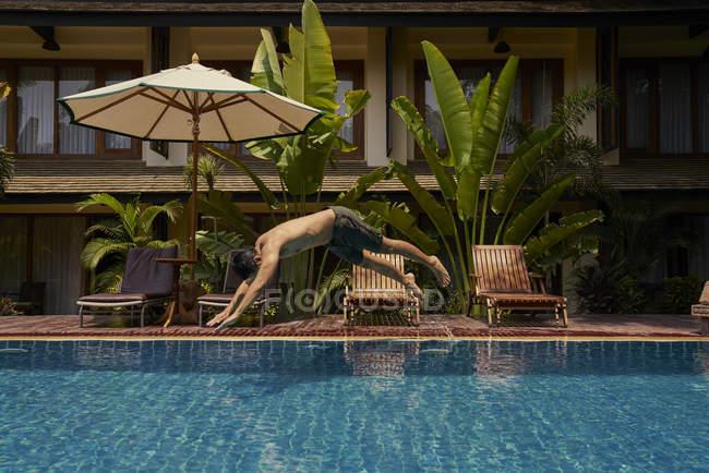 Giovane tuffo in piscina, vista laterale — Foto stock