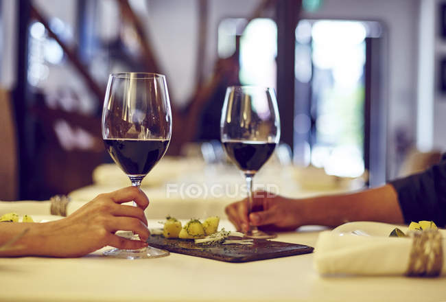 Cropped image young couple having date in cafe with wine — Stock Photo
