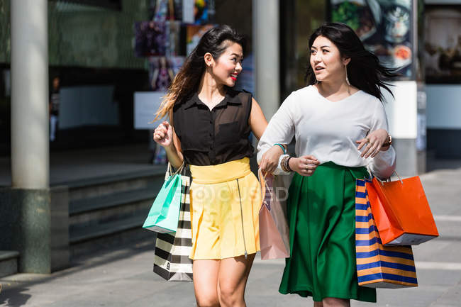 Giovani donne che fanno shopping e si divertono insieme . — Foto stock