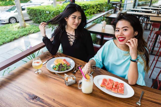 Mujeres jóvenes comiendo en un café juntas . - foto de stock