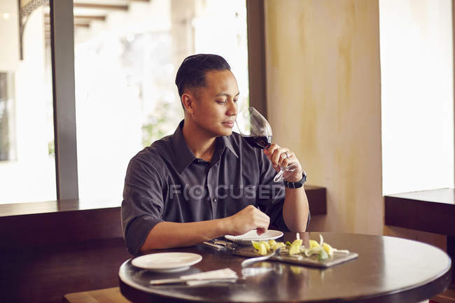 Young asian handsome man in cafe with wine — Stock Photo