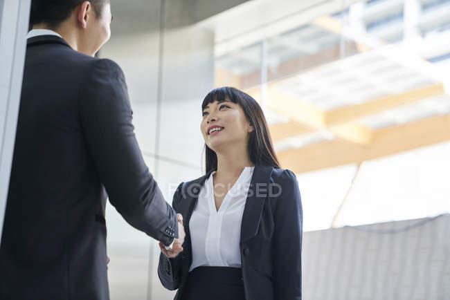 Молодая азиатская бизнес-пара пожимает руки в современном офисе — стоковое фото