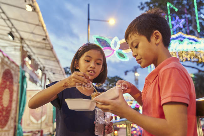 Siblings breaking fast at Hari Raya bazaar, Singapore — Stock Photo