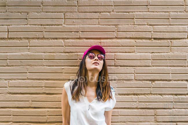 Молодий привабливою азіатські жінки в сонцезахисні окуляри і рожевий cap — стокове фото