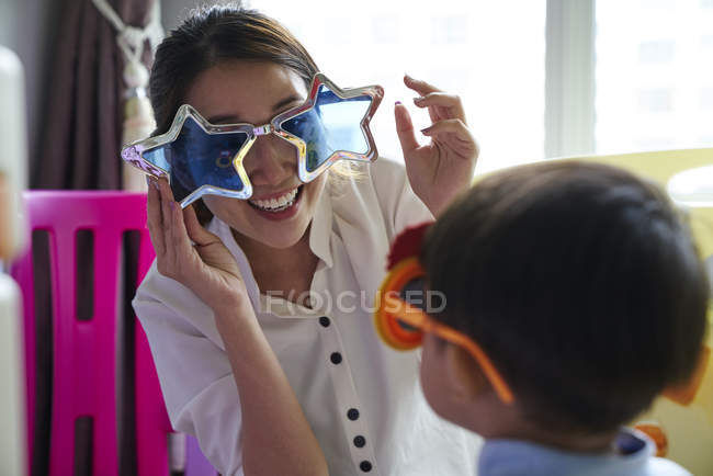 Asian mother and son bonding with fun glasses — Stock Photo