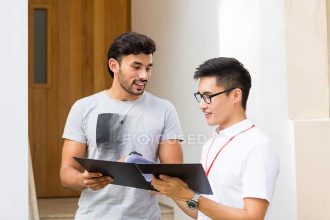 Maschio venditore intervistando asiatico adulto uomo — Foto stock