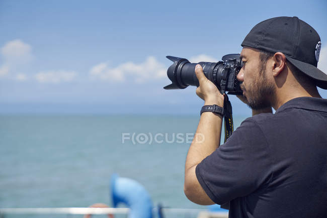 Young man taking photos with camera — Stock Photo