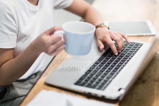 Image recadrée de femme à l'aide d'ordinateur portable au bureau — Photo de stock