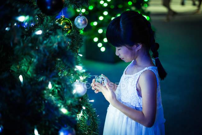 Счастливая азиатская девушка играет с пузырьком возле елки в парке развлечений на Рождество — стоковое фото