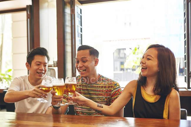 Щасливі молодих азіатських друзі пити пиво в м. бар — стокове фото