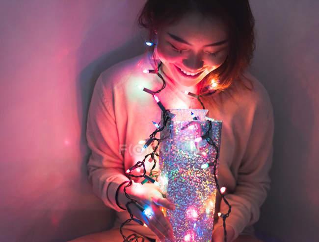 Joven mujer asiática relajándose en casa con guirnalda de Navidad - foto de stock