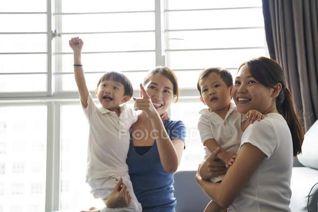 Молодые матери сближаются со своими детьми в гостиной — стоковое фото