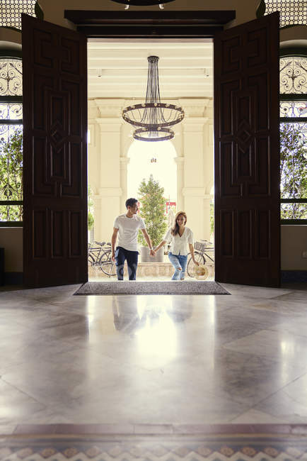 Happy young asian couple walking in building and holding hands — Stock Photo