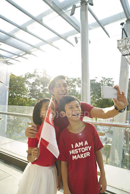 Happy family celebrating singapores national day — Foto stock
