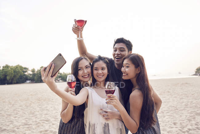 Attractive young asian friends taking selfie at beach — Stock Photo