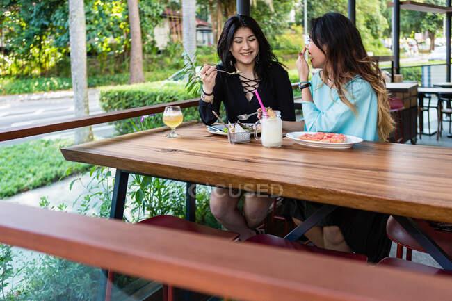 Jeunes femmes prenant un repas dans un café ensemble . — Photo de stock