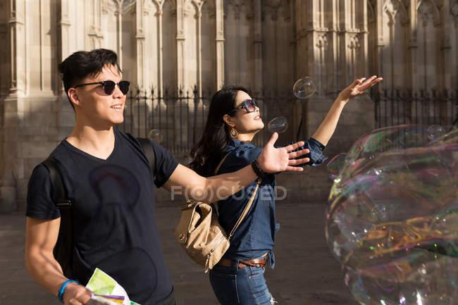 Chinesisches Ehepaar in Barcelona spielt mit Seifenblasen, Spanien — Stockfoto