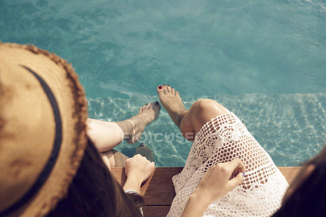 Attractive young asian women relaxing near pool — Stock Photo