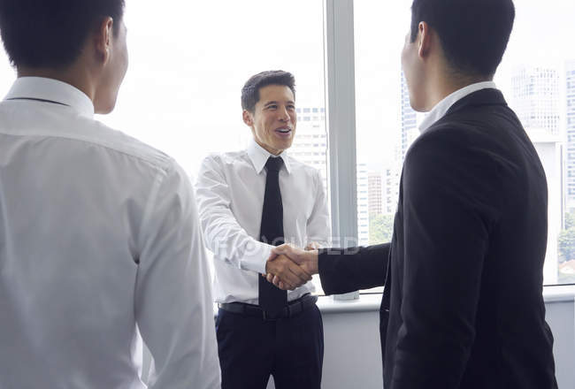 Young asian business men shaking hands at modern office — Stock Photo