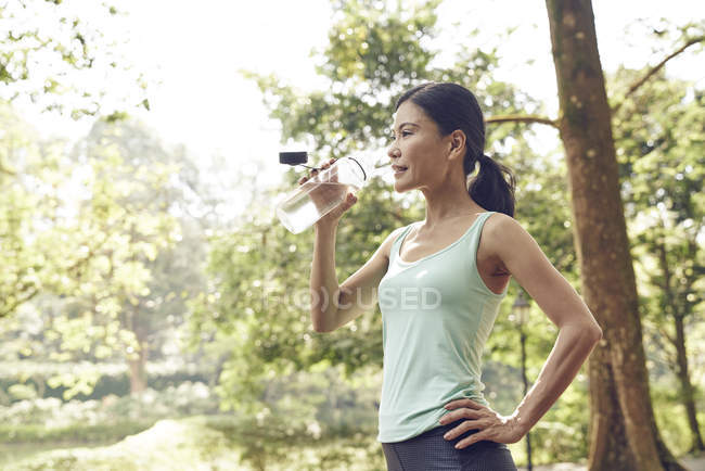 Женщина увлажняется после тренировки — стоковое фото
