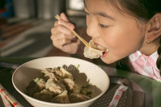 Little asian girl eating food in cafe — Photo de stock