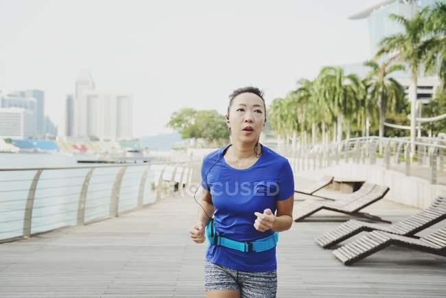 Молодая спортивная женщина бегает по парку — стоковое фото