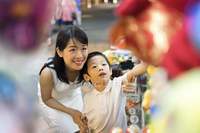 Jovem mãe e filho à procura de presentes — Fotografia de Stock