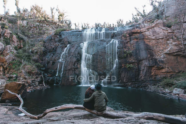 Young travelling couple enjoying waterfall — Stock Photo