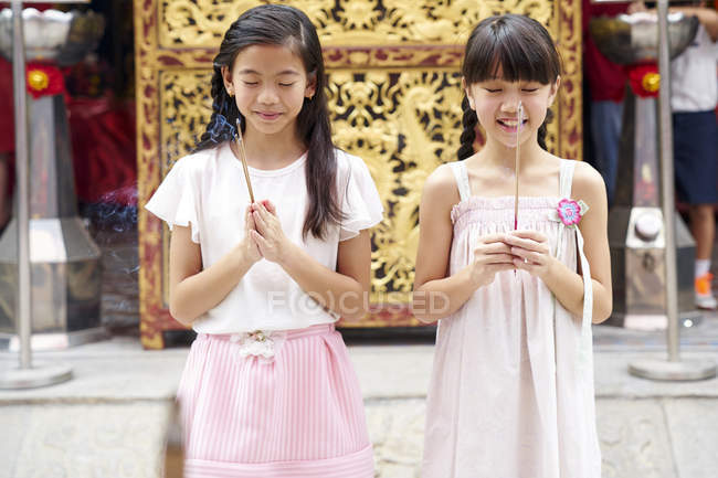 Happy asian sisters praying together in traditional Singaporean shrine — Stock Photo