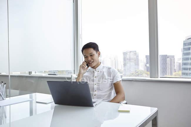 Hombre de negocios asiático joven en el trabajo en la oficina moderna - foto de stock