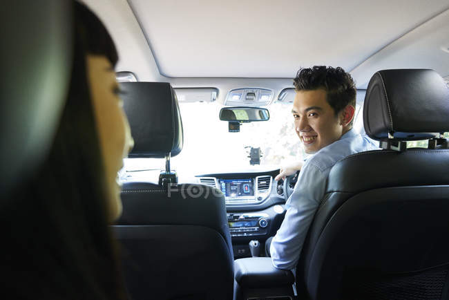 Driver smiling at his passenger in the backseat - foto de stock