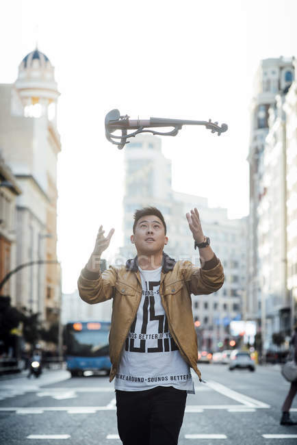 Young asian musician male throwing violin in the air at city — Stock Photo