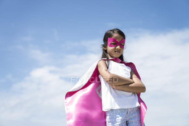 Young little cute asian girl posing in superhero costume against blue sky — Stock Photo